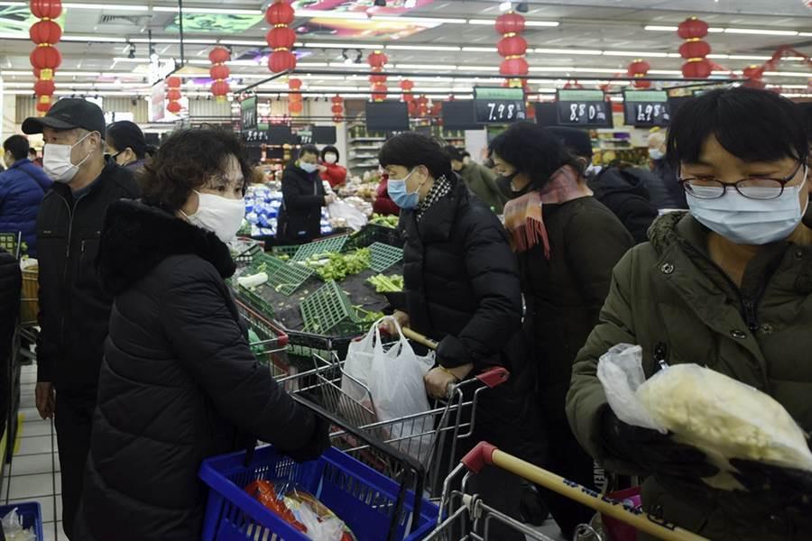 肺炎衝擊大陸經濟,導致內需與出口皆受阻。圖為民眾戴著口罩在超市購買商品。(美聯社)