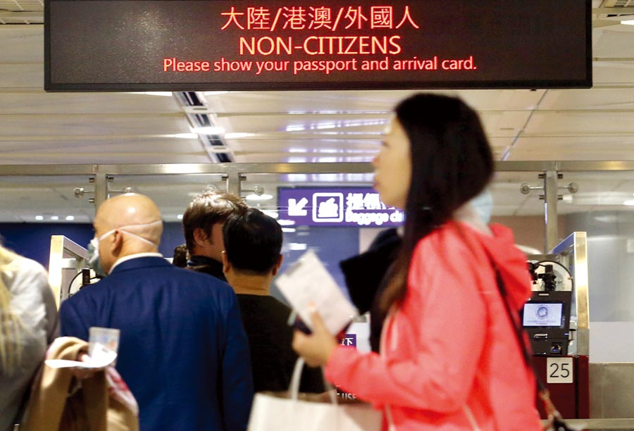 中央流行疫情指揮中心12日宣布,不具本國籍的陸配子女,且目前滯留陸港澳者,一律不予入境,一群外籍旅客12日在桃園機場,準備通關入境。(范揚光攝)