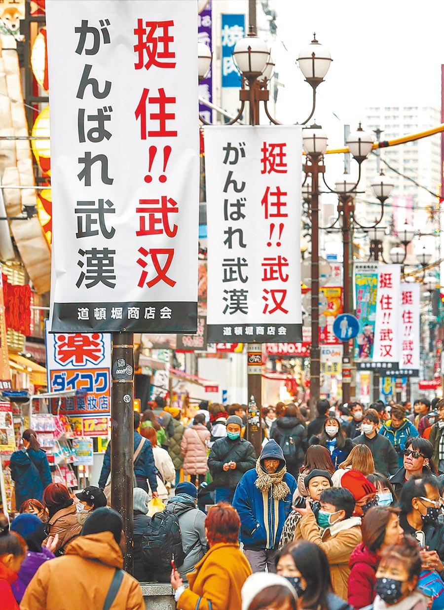 日本大阪道頓堀商圈的街道上,掛著「挺住!武漢」標語。(新華社)