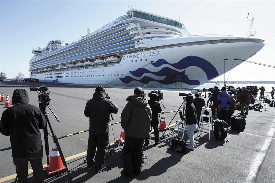 停泊在橫濱港的鑽石公主號郵輪外有許多媒體在守候。(美聯社)