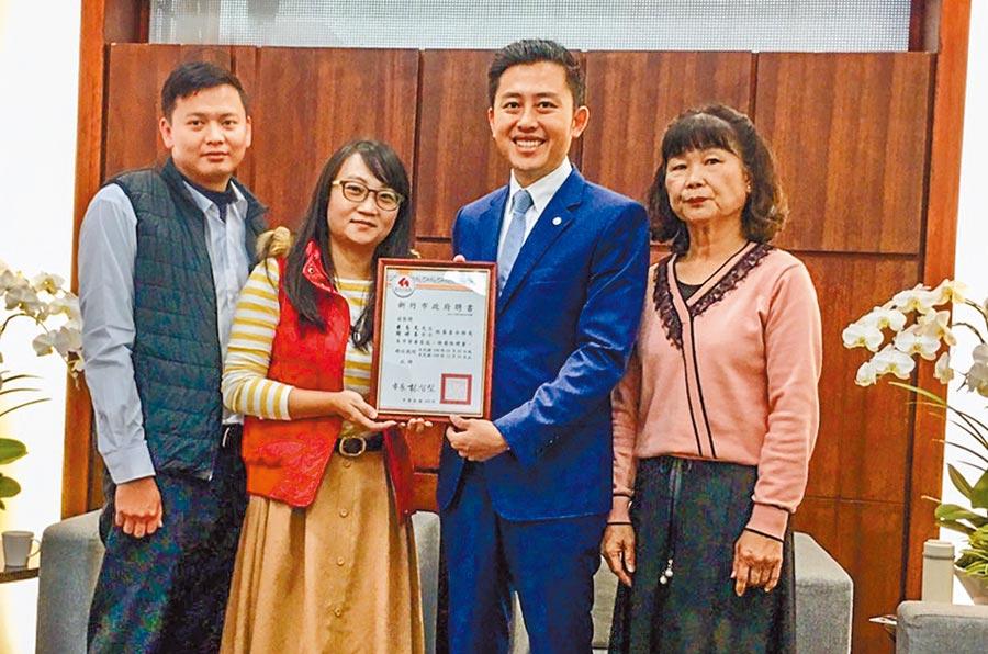 謝婷玉和其夫黃志文(左二及左)加入寄養家庭,是傳承邱麗雲(右)愛的信念,由市長林智堅(右二)頒給證書。(羅浚濱攝)