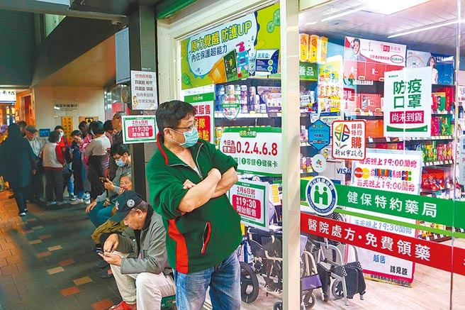 萬芳醫院旁的一家藥局為了方便上班族購買,晚上7點半開始販賣口罩,入晚6點藥局旁的騎樓早已大排長籠。(鄧博仁攝)