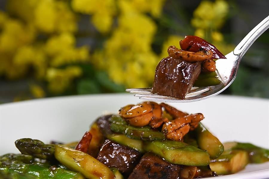 何競業料理的〈香辣蘆筍美國牛柳粒〉,用了〈黑胡椒焦糖腰果〉豐富口感,帶著鍋香鑊氣上桌,格外誘人食慾。(圖/姚舜)