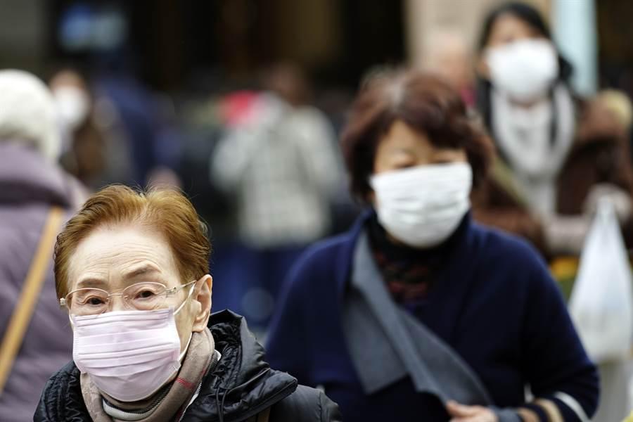 日本陸續傳出新冠肺炎疫情,行走在東京街頭的民眾紛紛戴上口罩。(美聯社)