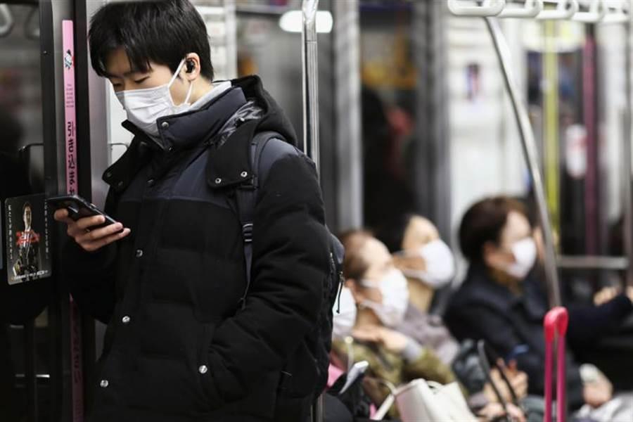 日本民眾14日紛紛在東京的電車上載口罩。(路透)