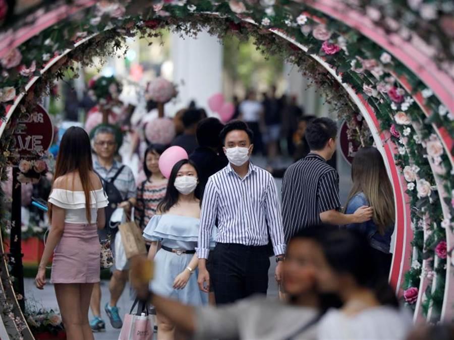 新加坡一對情侶14日戴口罩上街,慶祝情人節。(路透)