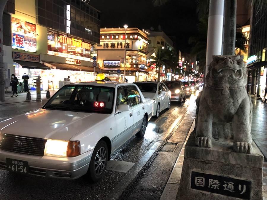 日本沖繩縣那霸市的國際通一直是觀光客聚集的地方,計程車排班的情形也常見。(黃菁菁攝)