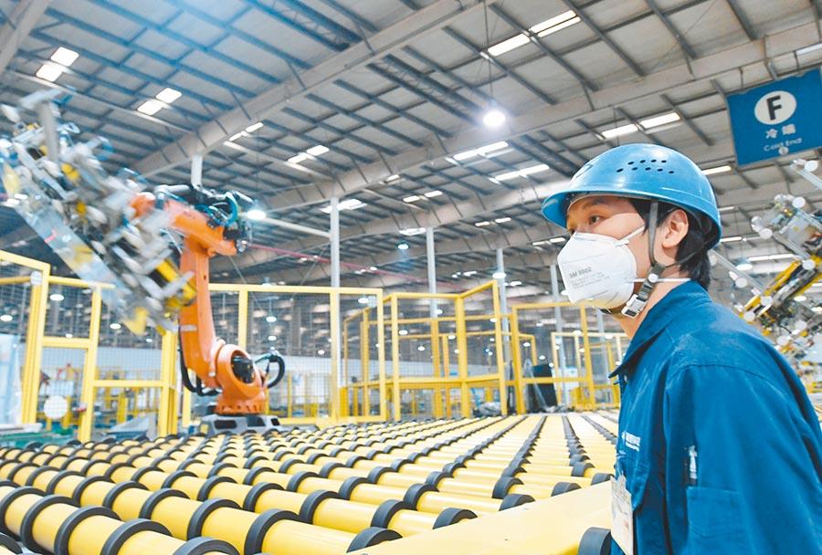 福建省福清市防控生產兩不誤。圖為2月12日,在福耀玻璃集團汽車玻璃生產流水線上,工人戴著口罩查看機器人生產。(新華社)