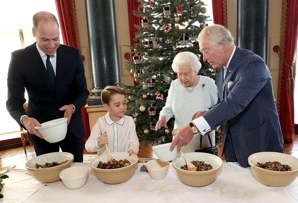 小王子喬治2019年12月時,在爸爸威廉(左),還有身為曾祖母的女王,以及爺爺查爾斯王儲(右)的協助下,在白金漢宮做聖誕布丁。(達志圖庫/TGP)
