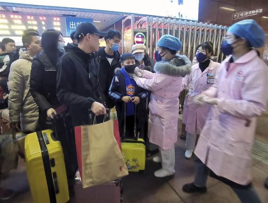 武漢肺炎疫情擴散,醫護人員1月22日在江西省南昌市火車站為旅客檢疫。(美聯社)