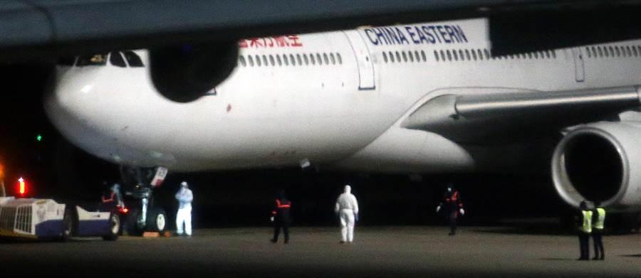 圖為滯留大陸武漢首批台商3日晚間搭機返台,穿著白色防護衣的防疫人員在機坪待命。(資料照,范揚光攝)