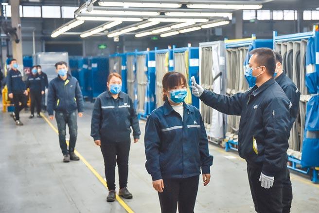北京北汽延鋒汽車部件有限公司復工,工人排隊測量體溫。(新華社)
