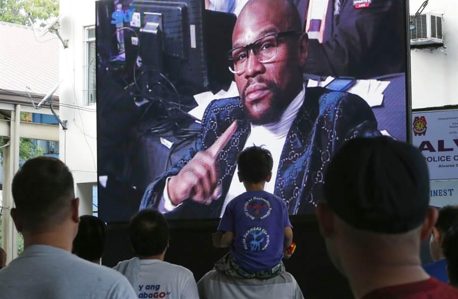 菲律賓觀眾戶外收看拳賽轉播,梅威瑟出現於畫面中。(美聯社資料照)