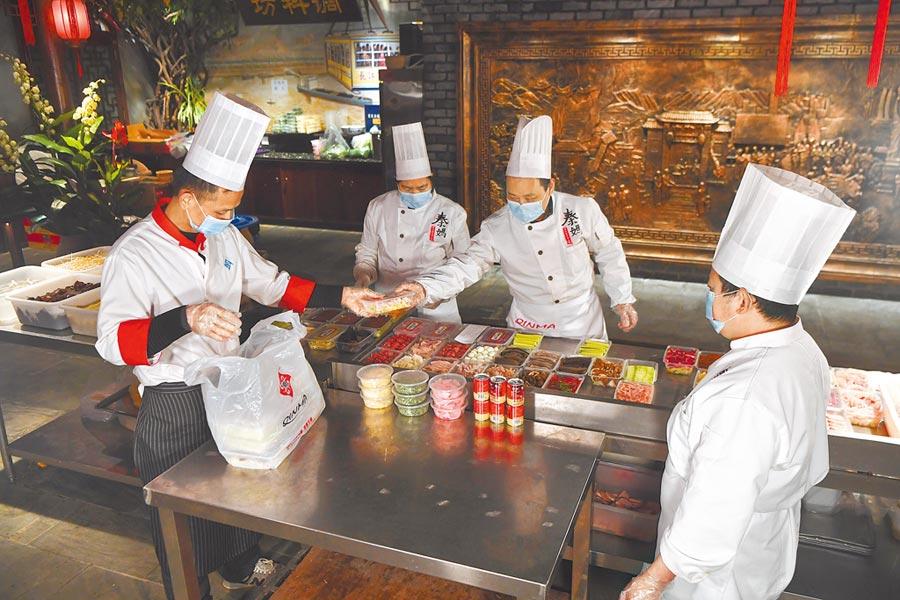 受疫情衝擊,潮汕牛肉火鍋也頂不住。圖為重慶一家火鍋店員工在打包外賣菜品。 (新華社)