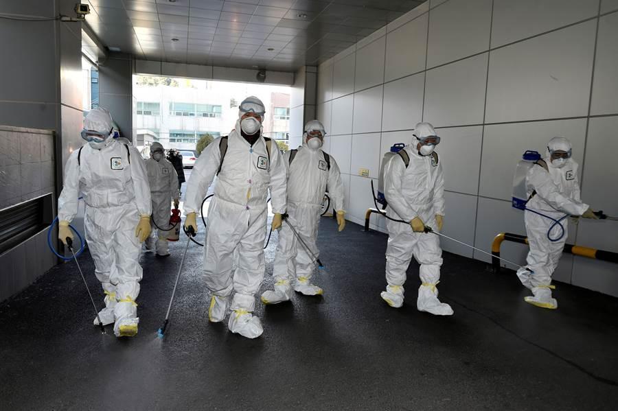 韓國大邱傳出31號新冠肺炎女病患曾去過新天地耶穌教會教堂後,防疫人員19日進行消毒的畫面。(路透)