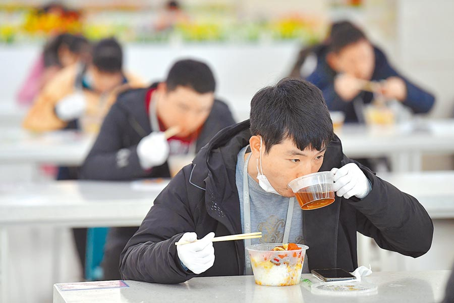 2月14日,南昌某企業員工在餐廳分桌用餐。(新華社)