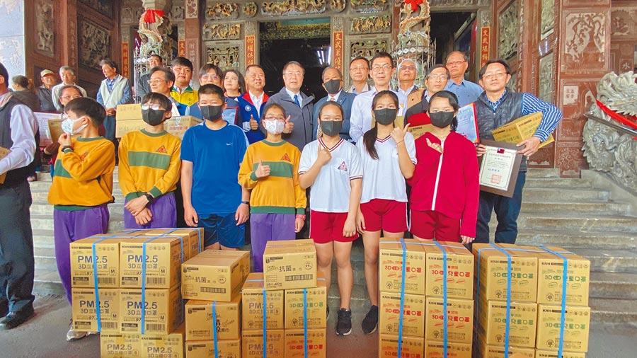 康那香董事長戴榮吉(第二排戴口罩者)贈送區內學童及漚汪文衡殿65歲以上信徒防疫口罩及抗菌溼巾。(劉秀芬攝)