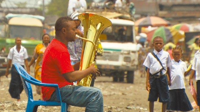 位於非洲剛果民主共和國的首都金夏沙,在內戰後一片狼藉,業餘音樂家在街頭上演奏音樂,安慰人心。圖為紀錄片《金夏沙交響夢》裡的一幕。(台灣國際紀錄片雙年展提供)