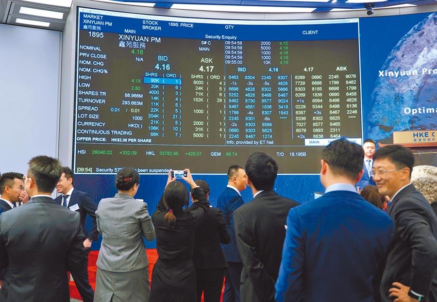 詐騙集團操縱「仙股」股價暴起暴落。圖為出席港交所上市儀式的嘉賓在看盤。(中新社)