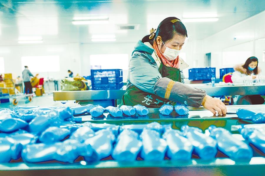 2月22日,位於重慶市南川區的一家企業乙醇消毒液生產線上,復工的工人正忙碌工作。(新華社)