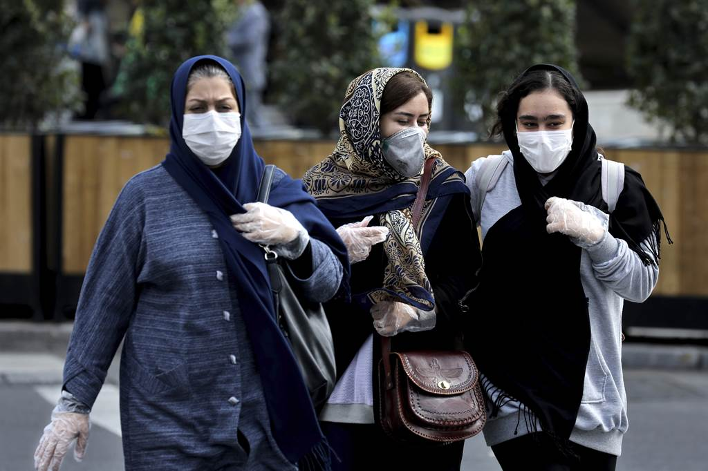 伊朗爆發新冠肺炎疫情,民眾2月23日戴著口罩,走在德黑蘭鬧區。(美聯社)