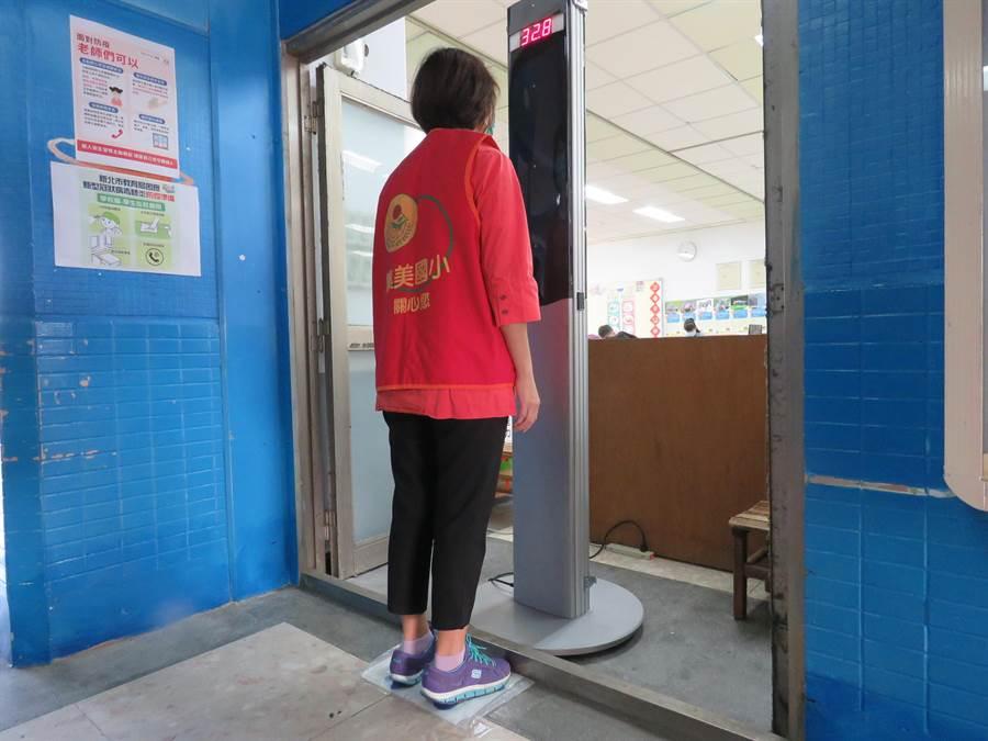 三重區集美國小租用1台醫用「直立式測溫儀」,為校內數百位教職員工量體溫。(吳亮賢攝)