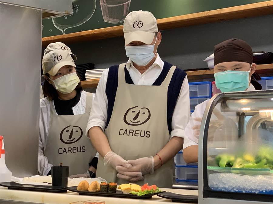 高雄市長韓國瑜(中)今天獻出壽司DIY處女秀,希望拉抬喜憨兒料理生意。(柯宗緯攝)