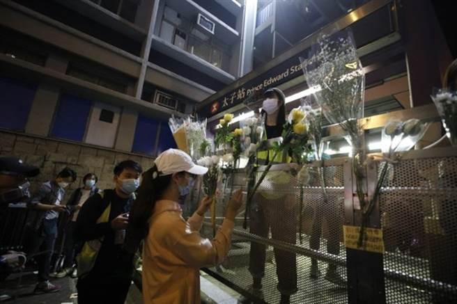 香港群眾在太子站前地上與圍欄上擺放鮮花悼念「831」事件半周年。(圖/東網)