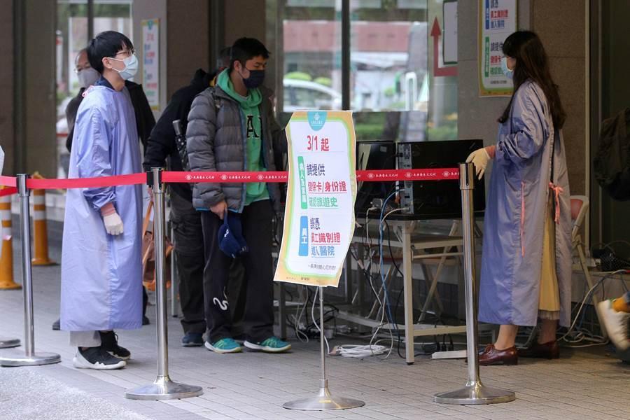 長庚醫院台北院區2日在大門豎立告示牌,並安排人員身穿防護裝備檢查進入民眾有無相關旅遊史。(黃世麒攝)