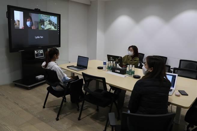 北京一家企業員工在會議室內,和居家隔離的同事進行視訊會議。(圖/中新社)