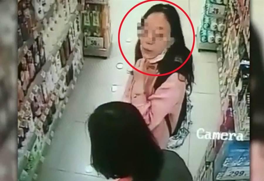 香港網友在臉書社團貼出影片,一名中年女疑似故意拉下口罩,朝店員吐口水。(截自東網畫面)