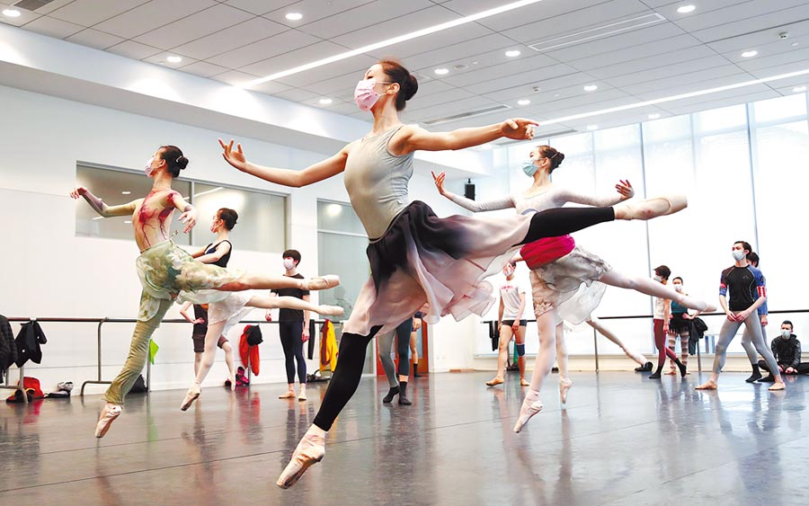 3月2日,上海芭蕾舞團的演員們在排練廳戴著口罩起舞 。(中新社)