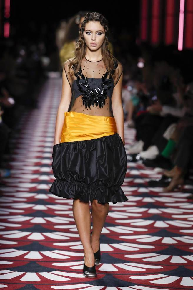 艾莉絲洛身穿網紗拼接透膚洋裝,大秀緊實身材。(MIUMIU提供)