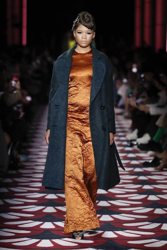 柿子色的綢緞連衣裙外罩綠色粗花呢大衣,利用撞色展現女性力量。(MIUMIU提供)