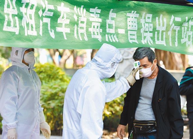 大陸減免計程車規費。圖為2月21日,廣州為計程車司機測量體溫。(新華社)