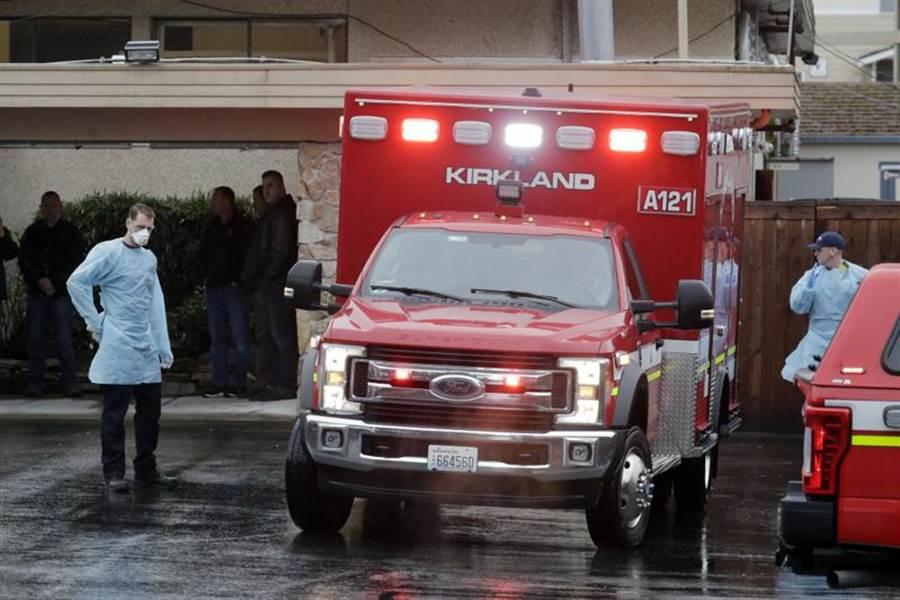 美國華盛頓州「柯克蘭長照中心」(Life Care Center of Kirkland)不斷傳出確診與死亡病例,圖為工作人員6日站在救護車旁的畫面。(美聯社)