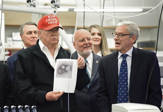 美國總統川普在疾病控制中心的記者會上拿著一張新冠病毒照片向媒體展示,他至今不願承認新冠病毒疫情的嚴重性,可能是怕影響股市,進而危及其連任。(圖/美聯社)