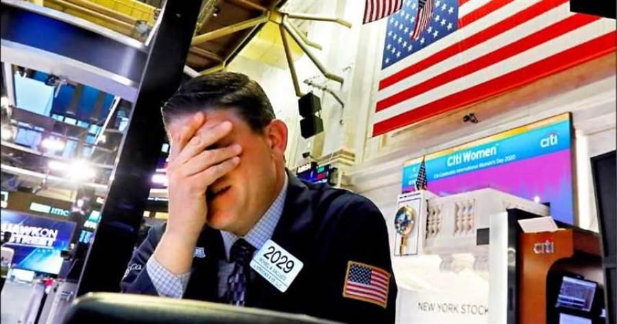美股收盤道瓊狂挫逾2000點,一位紐交所交易員,也難過掩面不敢繼續看下去。 (圖/美聯社)