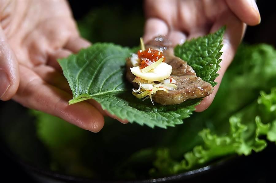 韓國紫蘇葉有一股特殊且明顯的香氣,用它包捲燒肉並搭配蒜片、薑絲或青辣椒絲,以及一點點自製「包飯醬」,一口吃下、非常過癮。(圖/姚舜)