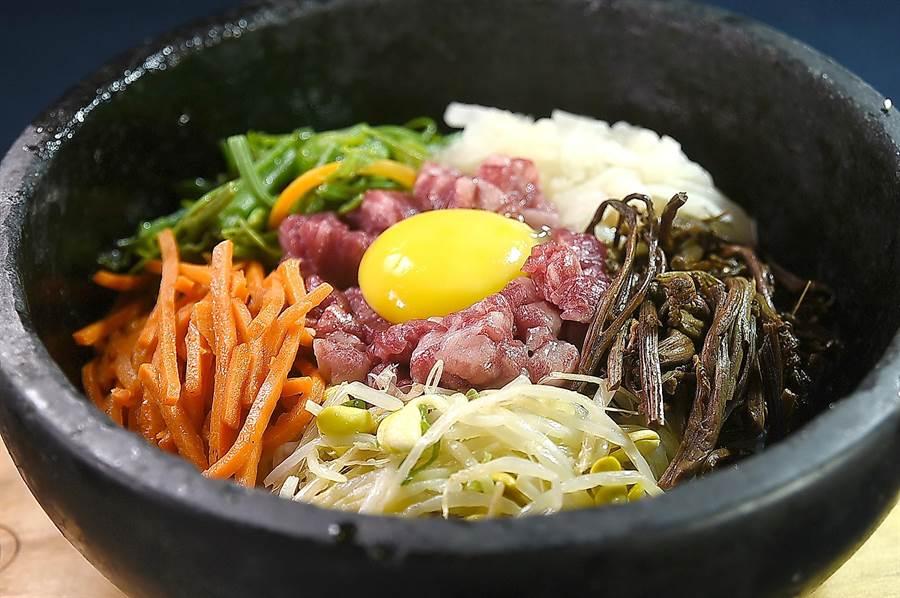 〈兩班家〉韓式燒烤的〈石鍋拌飯〉,是晉州作法,利用滾燙石碗的溫度將生肉「拌熟」,且為凸顯牛肉鮮甜,餡料不會太多,其中並有韓國的醃漬蕨菜,風味更正統道地。(圖/姚舜)