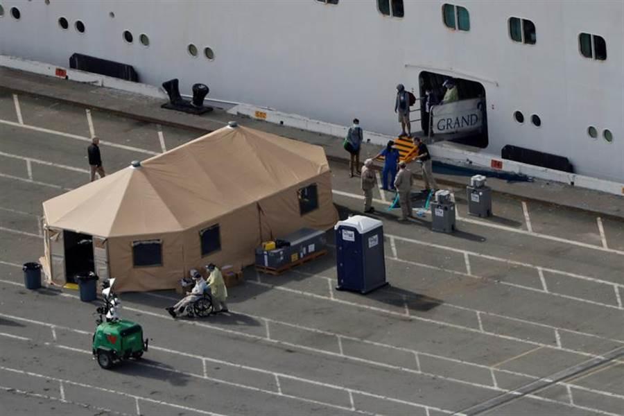 「至尊公主」號郵輪9日終於獲准停靠加州奧克蘭港(Port of Oakland),戴著口罩的乘員陸續下船。(路透)