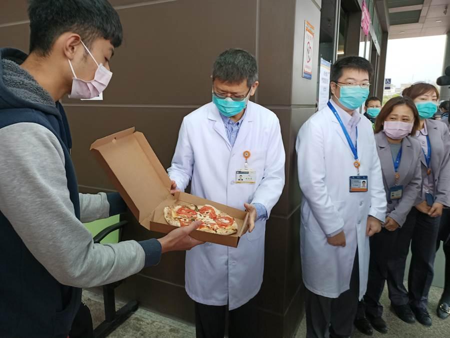 宜大學生曾品均邀約已畢業的學長林聖翔,一同到陽大醫院門口現場烤製披薩並贈送給醫護人員,表達 鼓勵與支持。(胡健森攝)