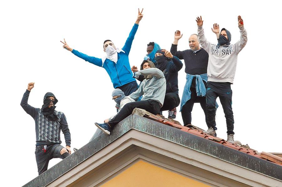 義大利政府為抗疫祭出封鎖1600萬人的非常手段,監獄因配合執行禁止探監措施,多處監獄8日爆發受刑人騷亂,造成至少6死。圖為米蘭聖維托雷監獄的囚犯,9日爬上屋頂抗議。(美聯社)