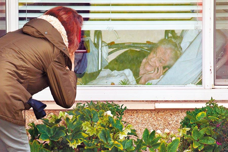一名女子8日在美國華盛頓州柯克蘭長照機構「生命護理中心」外,用手機與住在該中心的81歲母親通話。華盛頓州新冠肺炎死亡病例已增至19例,其中16人與這家長照中心有關。(路透)