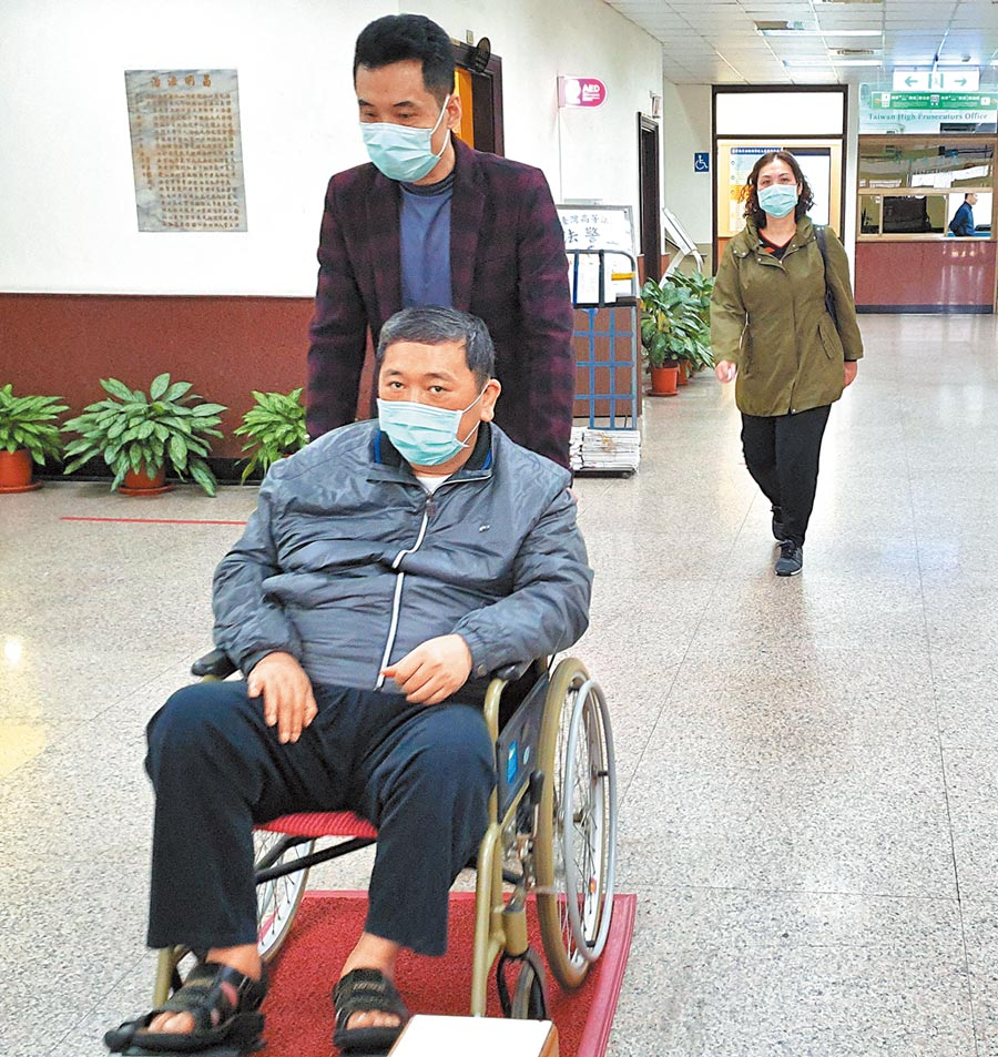 前桃園縣議員鄧文昌坐輪椅由家人陪同應訊,眼神仍不時露出驚恐。(林偉信攝)