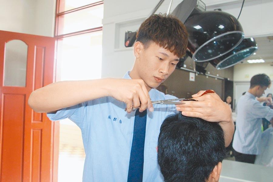 中興商工時尚造型科張羣岳對美髮深感興趣,今年成功考取男子理髮乙級證照,9日展現超齡理髮技巧。(何冠嫻攝)