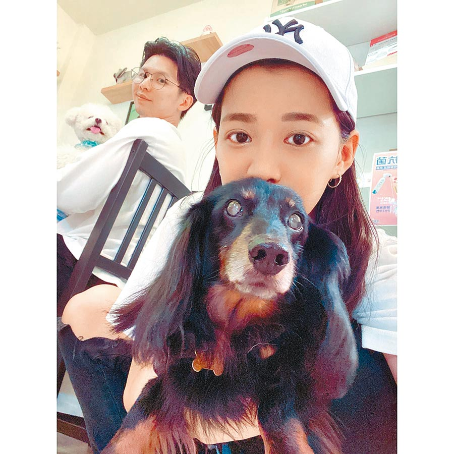 王思平(前)與老公李世偉分別抱著愛犬,開心宣布自己要當媽媽了。(摘自臉書)