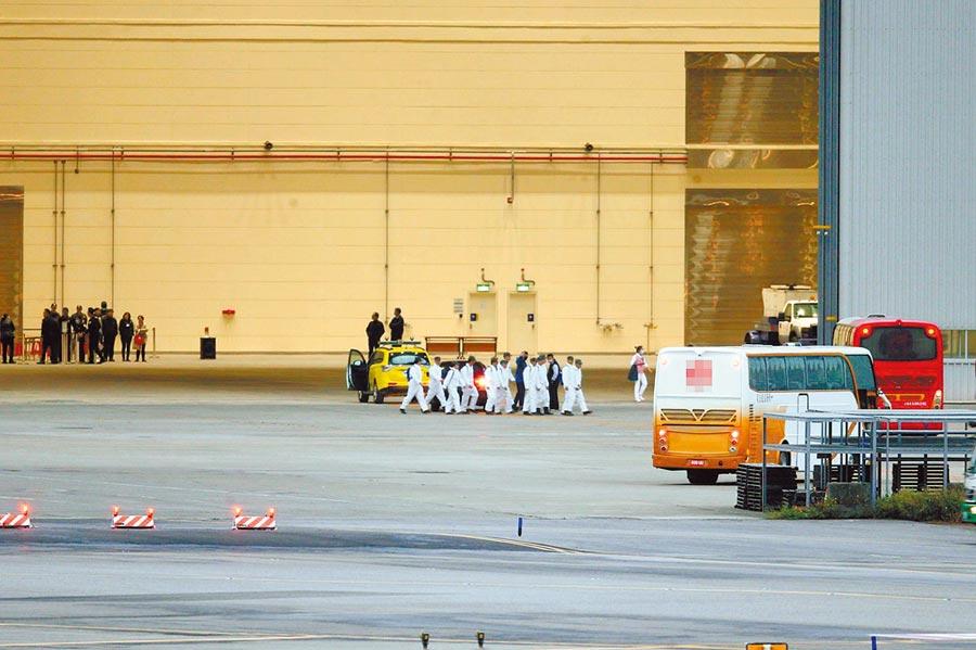 第二批武漢包機10日深夜抵台,多輛遊覽車在傍晚即陸續抵達桃園機場,進入台飛維修棚場,準備接送旅客至隔離處所,工作人員也穿上防護衣,進行前置工作。(陳麒全攝)