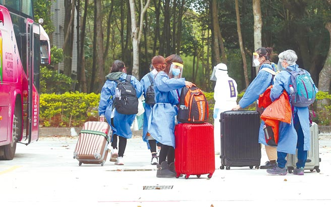 第二批武漢包機11日凌晨抵達桃園機場,機上旅客經檢疫及入境通關後,分批搭乘遊覽車前往隔離處所。(陳君瑋攝)