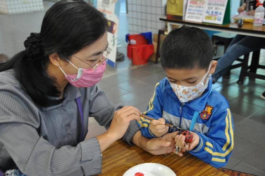 高雄社教館14日舉辦「彩繪種子DIY鑰匙圈」活動,親子們同心協力,共同創作出獨一無二的彩繪鑰匙圈作品。(洪浩軒攝)